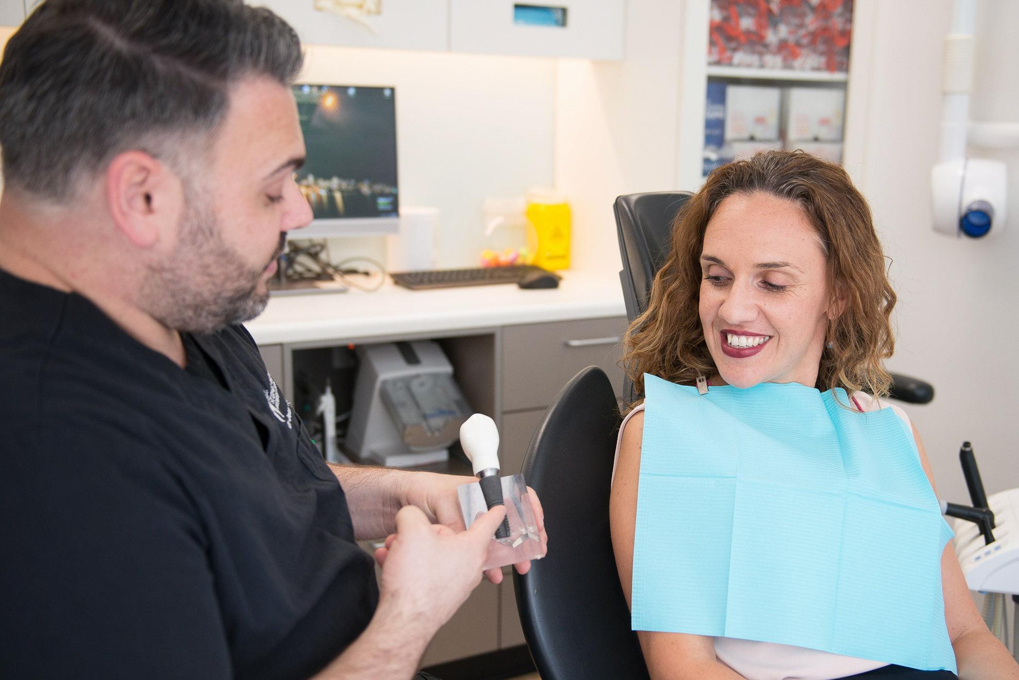 Dean showing Titanium implant model to patient